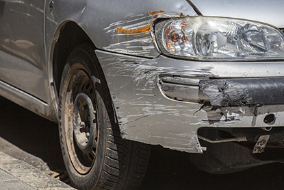 Scuffs and collision damage on grey vehicle front