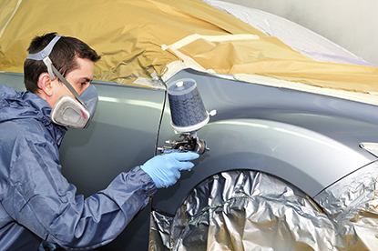 Male worker repainting the body of a grey vehicle